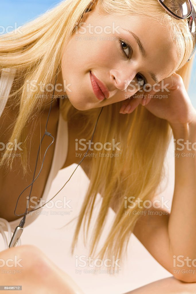 Young woman in bikini with cellphone or media player royaltyfri bildbanksbilder