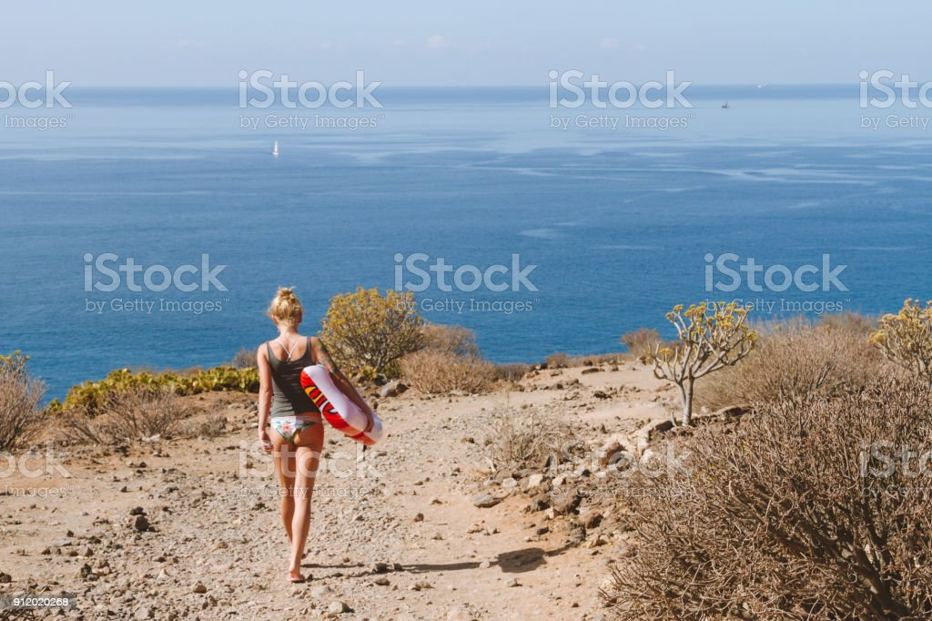 Young woman in bikini with pool float walking toward ocean - fotografia de stock