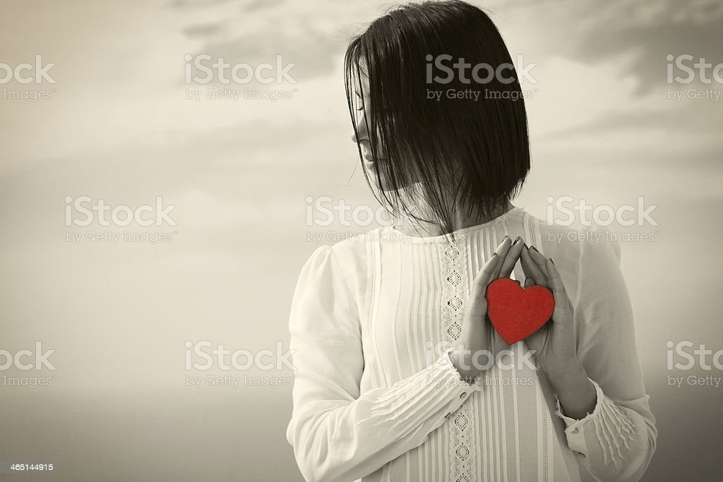Young woman in black and white holding a red heart shape stock photo