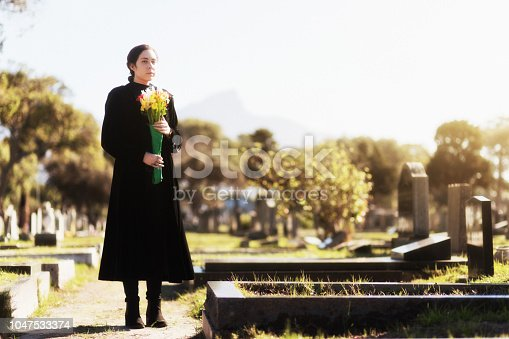 A young woman wearing black approaches a grave in a cemetery carrying flowers.