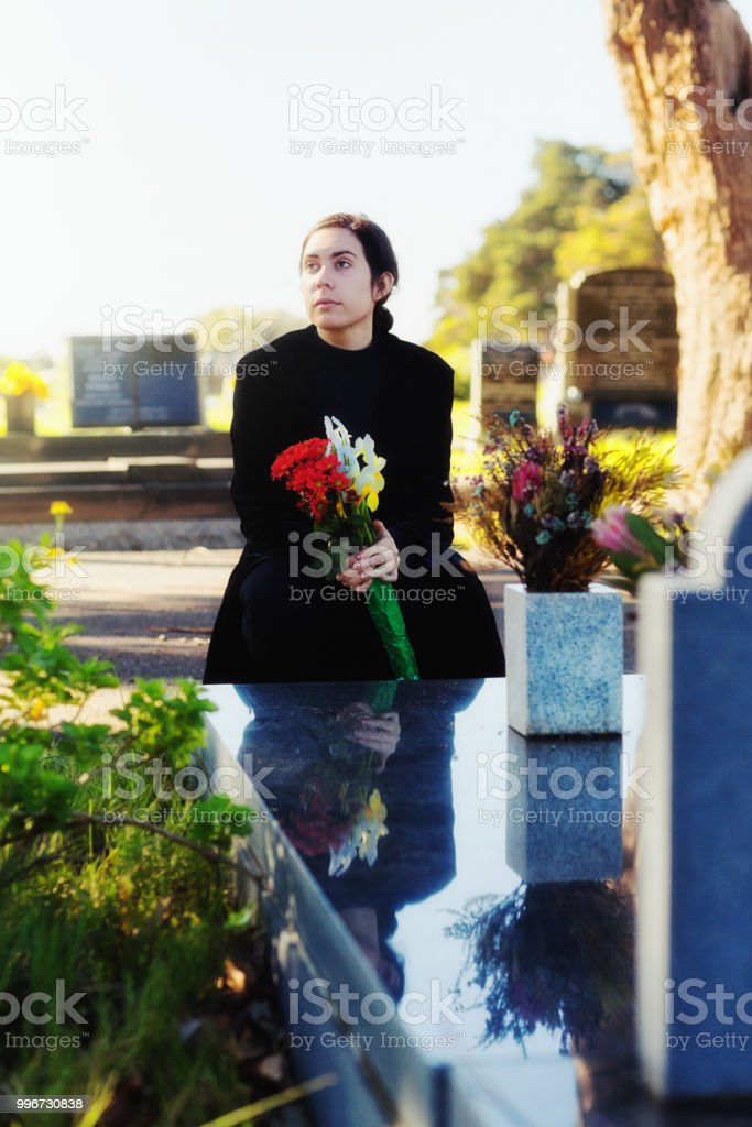 Young woman in black brings memorial bouquet to grave stock photo