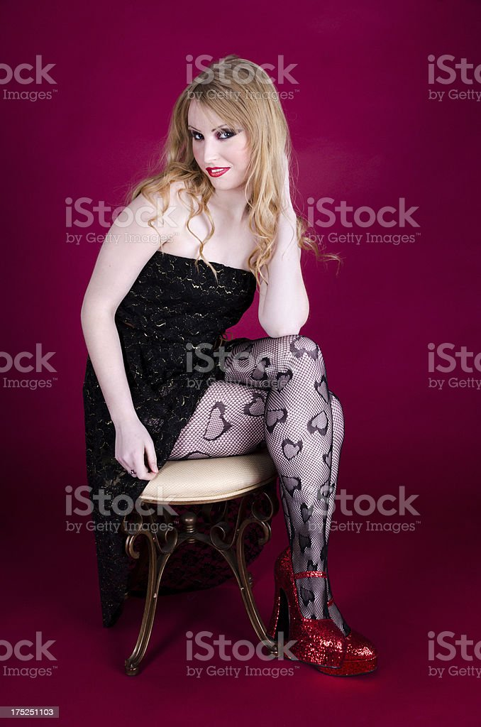 Young woman in black dress and red shoes royalty-free stock photo