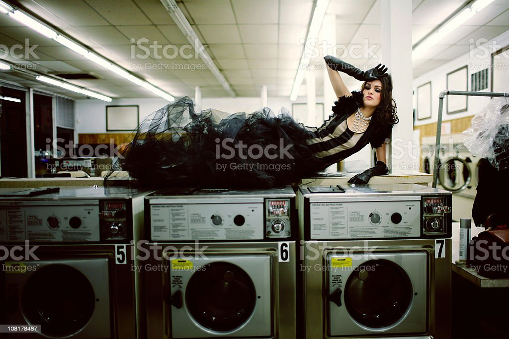 Young Woman in Black Gown Laying on Washing Machines royalty-free stock photo