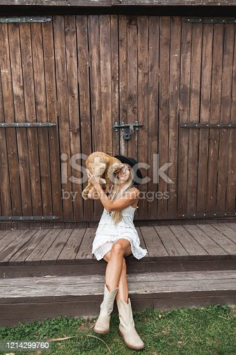 young woman in black hat, white boho dress and cowboy boots, sitting near an old barn and holding in hands big cute red cat. Countryside life, summer holidays.