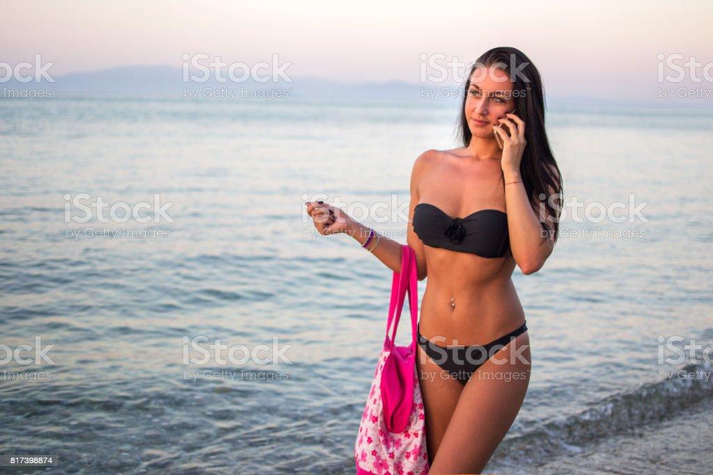 03baf8b95262 Mujer Joven En Traje De Baño Negro Con Bolso Hablando Por Teléfono ...