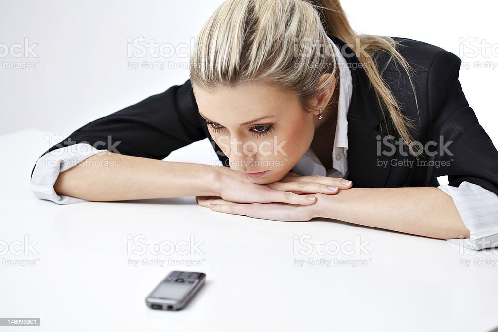 Young woman in blazer staring at cellphone sadly stock photo
