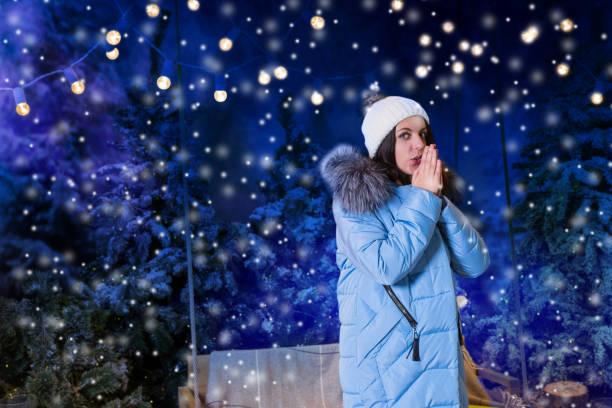 ダウン ジャケット手を地球温暖化と、夕方には雪に覆われた公園で懐中電灯の下でスイングの近くに立って青の若い女性 - ダウンジャケット ストックフォトと画像