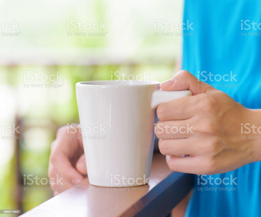 Ung kvinna i blå klänning njuter en mugg av dryck royaltyfri bildbanksbilder