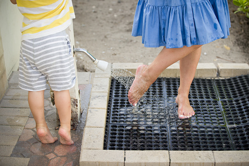 545091450 istock photo Young woman in blue dress washes the sand from her feet on white beach while her son is waiting for her nearby. Closeup of woman's legs under a beach shower. 1132338189