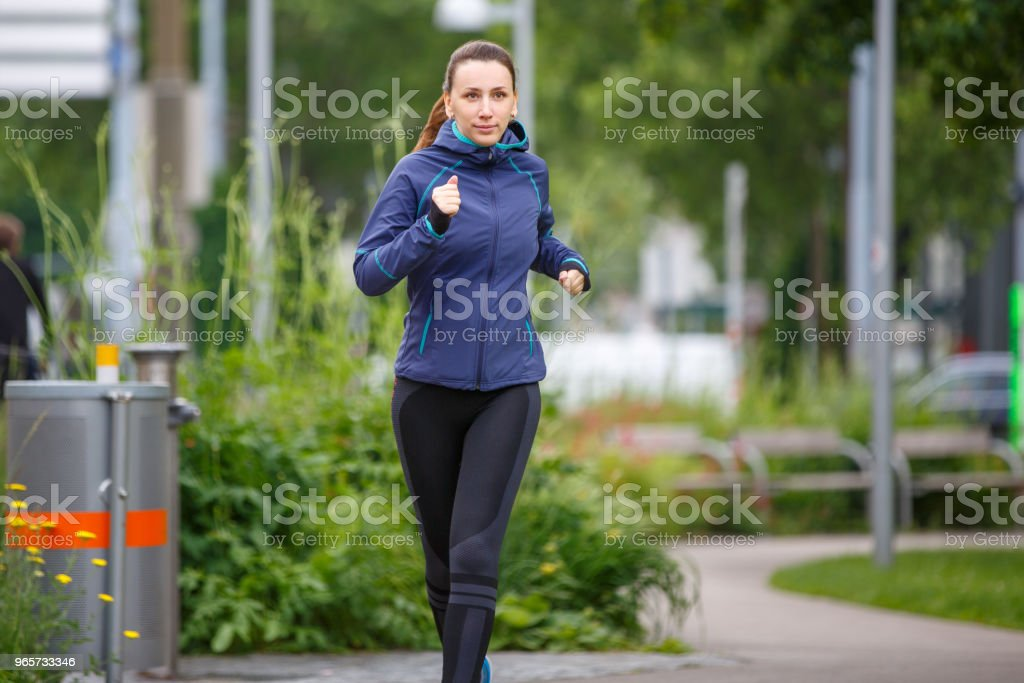Young woman in blue jacket jogging in park - Royalty-free Adult Stock Photo