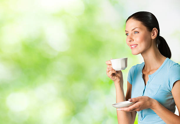 A young woman in blue smiling and drinking coffee outdoors stock photo