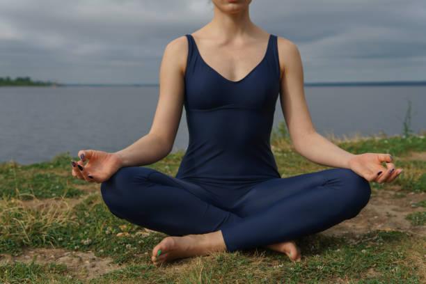 Junge Frau in blauen Sportbekleidung in Yoga-Pose, bewölktem Himmel und See im Hintergrund sitzt. – Foto