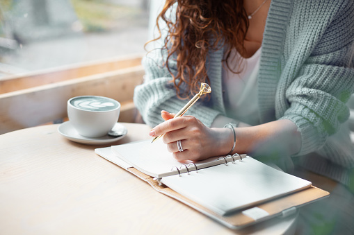 Young woman in blue warm sweater sitting near the big window of coffee shop and writing a Christmas shopping list with cup of blue latte. Planning Christmas holidays. Organising and planning concept.