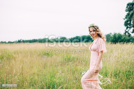 istock Young Woman In Boho Dress Standing On Meadow 637533120