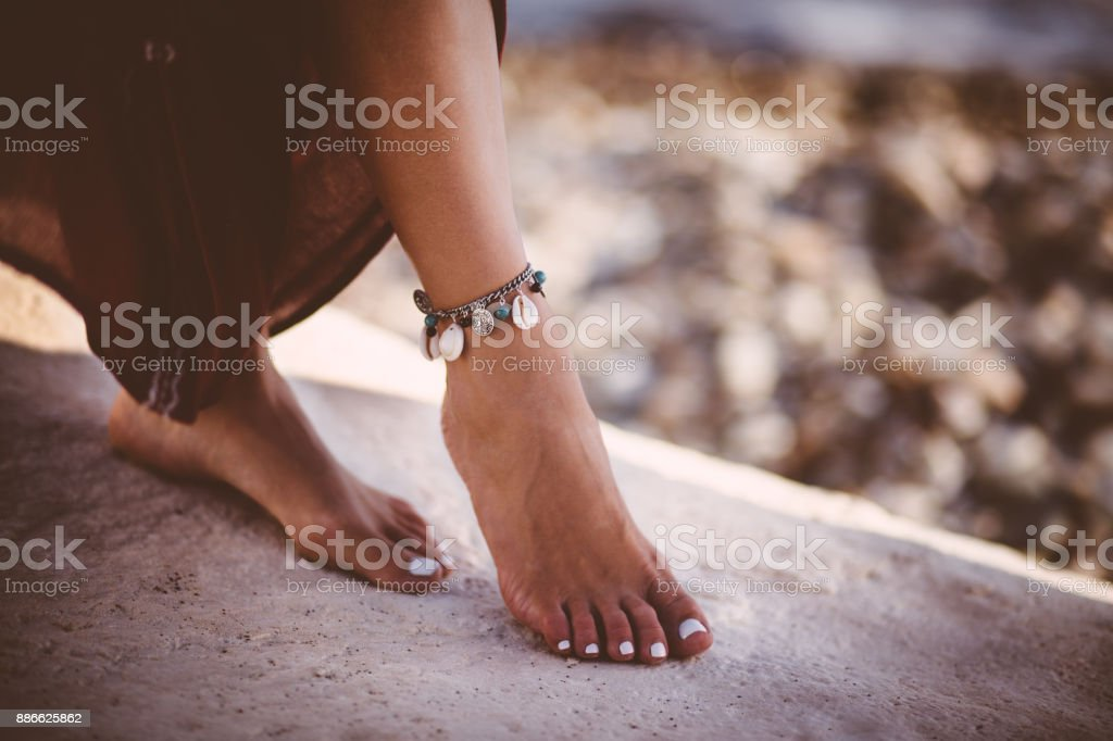 Young woman in boho style wearing silver ankle bracelet stock photo