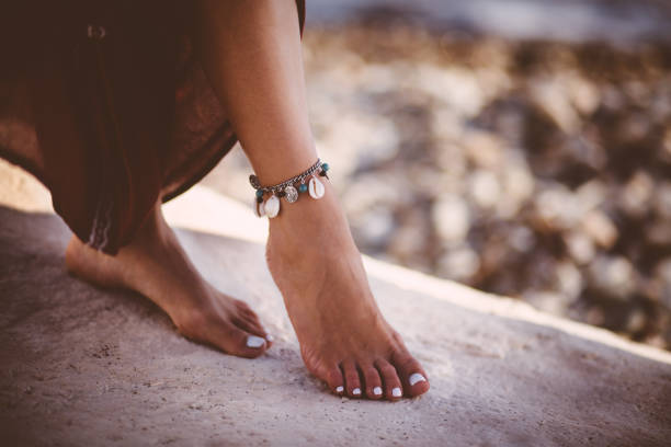 Young woman in boho style wearing silver ankle bracelet Close-up of young bohemian woman's foot wearing silver and turquoise ankle bracelet at the beach romani people stock pictures, royalty-free photos & images