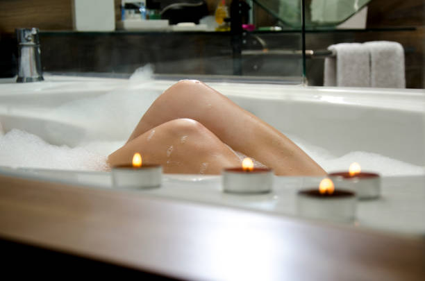 Young woman in bubble bath, illuminated candles in foreground stock photo
