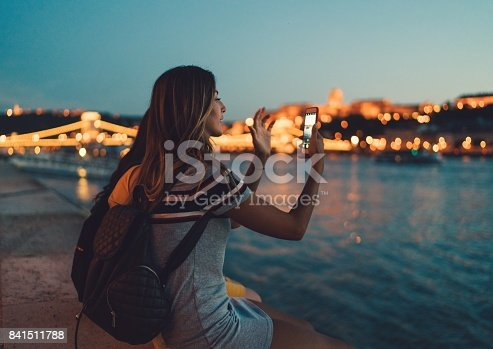 Tourist in Budapest taking photos with smartphone