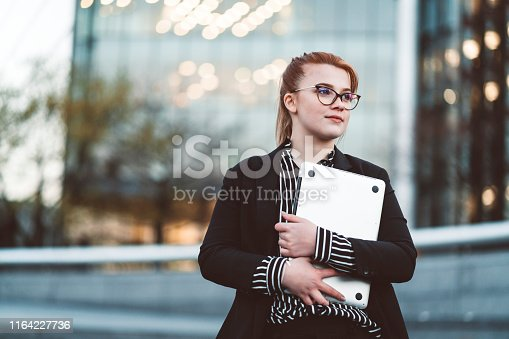 Young woman exchange student, working as an intern at a firm in London. Confident young woman with glasses holding a laptop.
