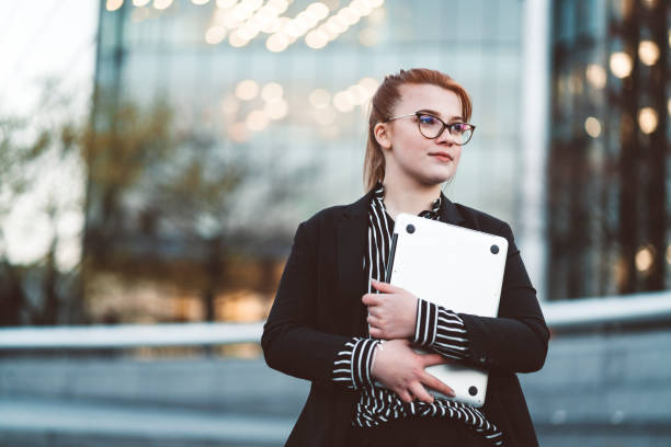 Young woman in business wear with glasses holding a laptop outdoors Young woman exchange student, working as an intern at a firm in London. Confident young woman with glasses holding a laptop. apprentice stock pictures, royalty-free photos & images