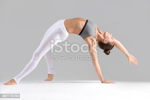 istock Young woman in Camatkarasana pose, grey studio background 637776764