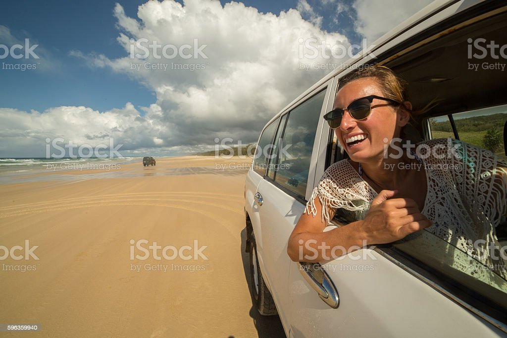 Young woman in car driving on sandy beach, Fraser Island royalty-free stock photo