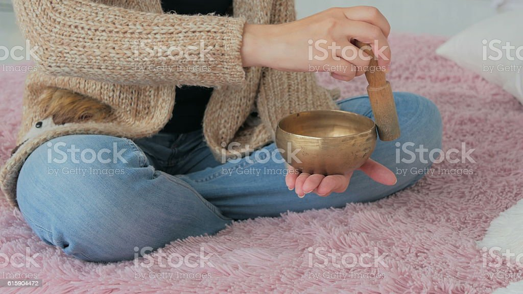 Young woman in cardigan relaxing with nepal singing bowl stock photo