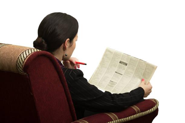 junge frau im sessel lesen einer zeitung mit einer werbeanzeige - medium strähnchen stock-fotos und bilder