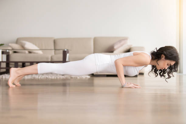 Young woman in chaturanga dandasana pose, hotel cozy living room Young attractive woman practicing yoga at home, standing in four limbed staff, Push ups or press ups exercise, chaturanga dandasana pose, working out, wearing white clothes, full length, living room namaskard geothermal area stock pictures, royalty-free photos & images