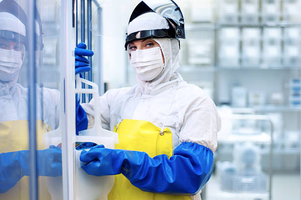 young woman in cleansuit and protective gear - white suit stock photos and pictures