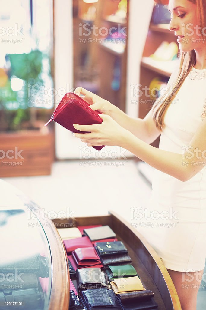 Young woman in clothing store checking new purse royalty-free stock photo