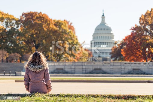 Young woman in coat sitting looking at view of United States Congress Capitol building, golden orange yellow foliage autumn fall trees on street during sunny day in Washington DC