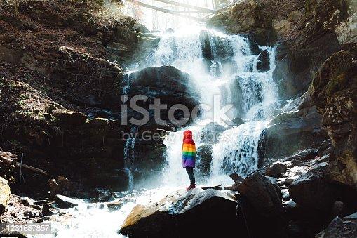 Woman traveler enjoying the sunny fresh spring view of the scenic waterfall in Carpathian mountains, Ukraine