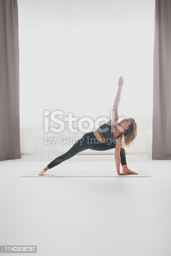 Side view of pretty young female performing Crescent Lunge exercise while doing yoga near window in stylish room