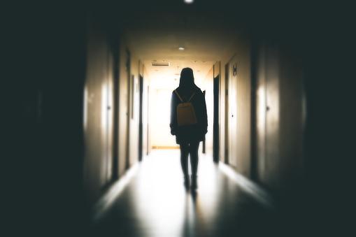 Young woman in dark building walkway
