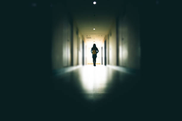Young woman in dark building walkway Young woman in dark building walkway harassment stock pictures, royalty-free photos & images