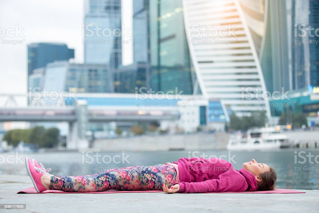 Young woman in Dead Body pose against the skyscraper stock photo