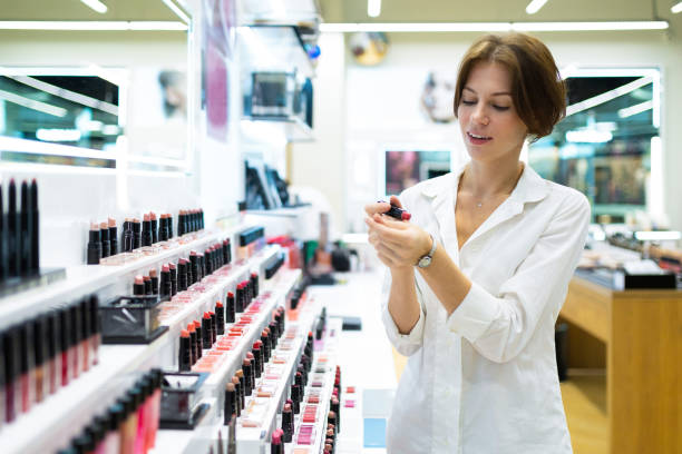 Young woman in decorative cosmetics shop is choosing lipstick stock photo