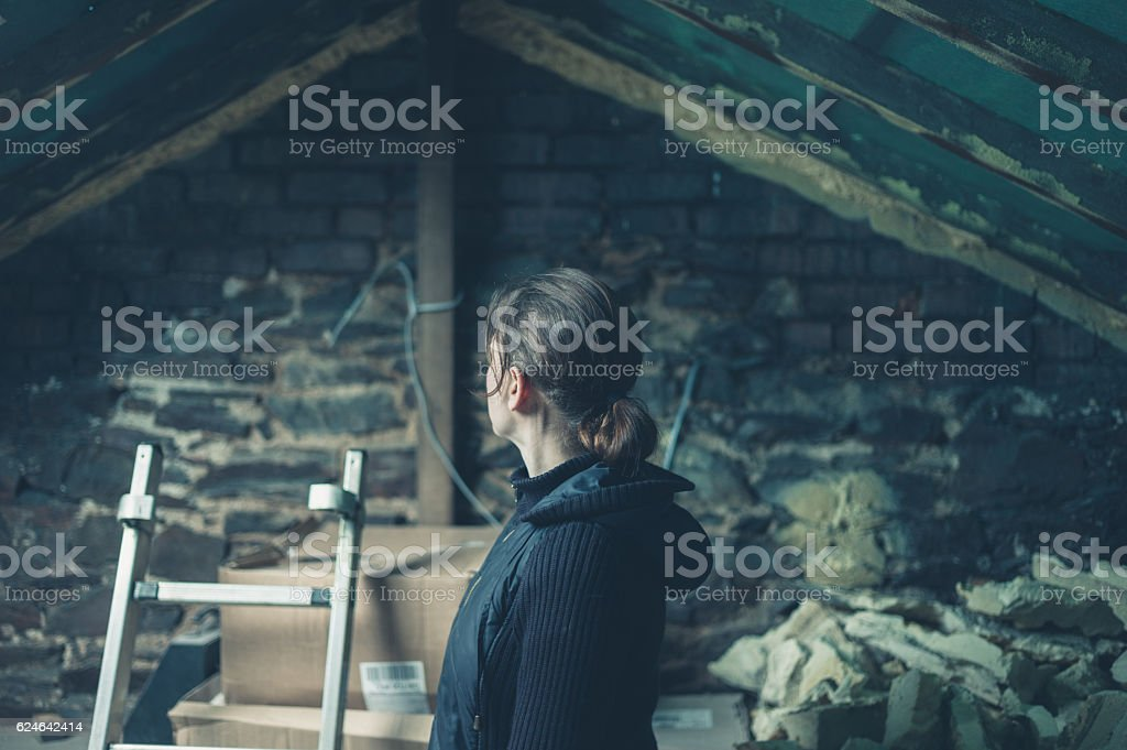 Young woman in derelict loft space stock photo