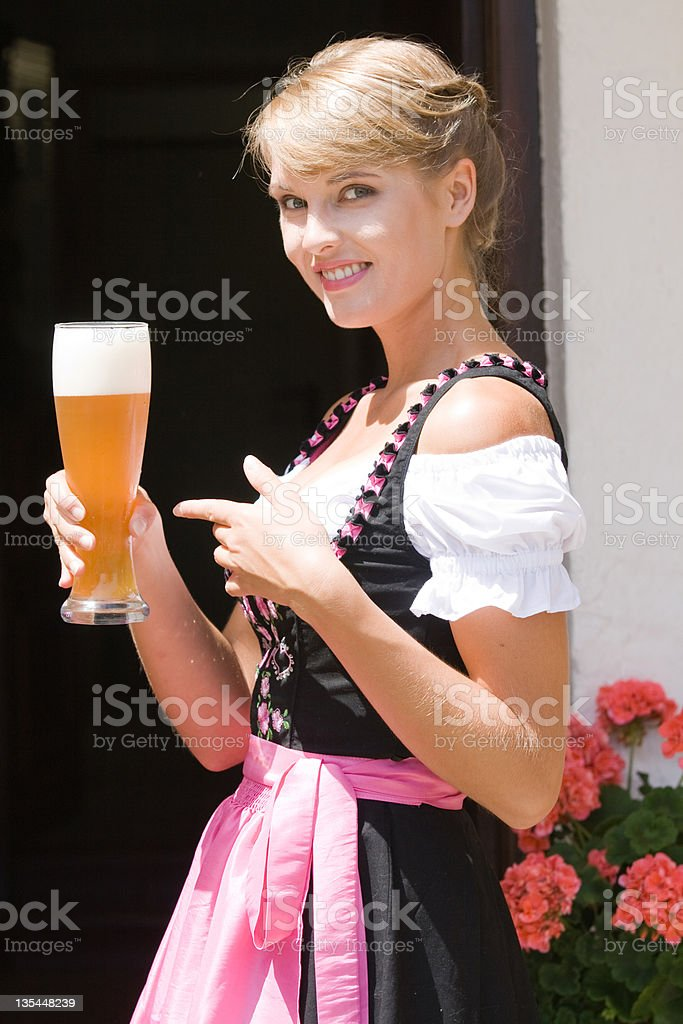 Young woman in dirndl with white beer royalty-free stock photo