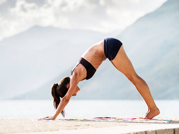 Young woman in downward facing dog position at coastline. stock photo