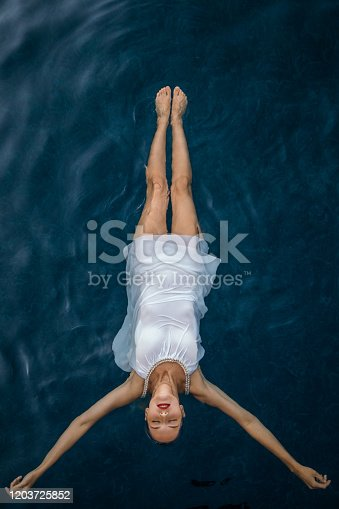 Attractive young woman with long blonde hair wearing white dress and floating on water surface. Soft light, and beautiful water color makes scene looks nice and tranquil. Photo taken from above