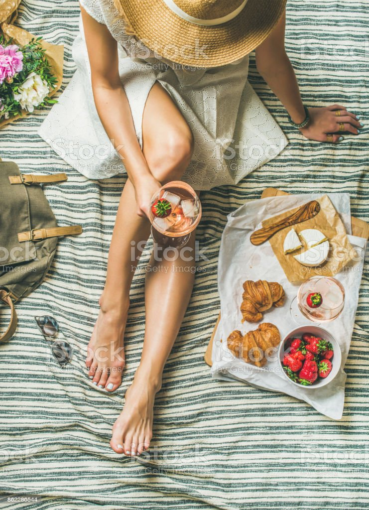 Young woman in dress sitting with wine and snacks stock photo
