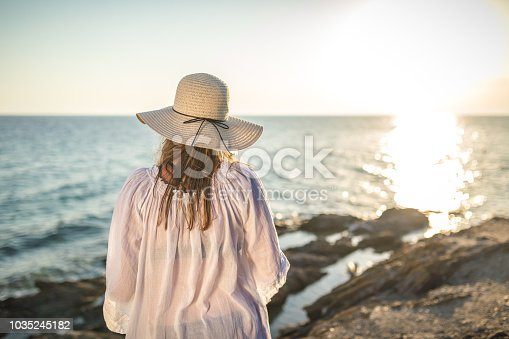 Young woman in dress standing by blue sea