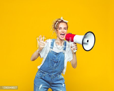 Portrait of excited young woman wearing white t-shirt, denim dungarees and bandana shouting into megaphone. Studio shot on yellow background.