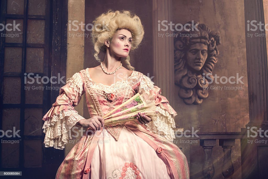 Young woman in eighteenth century image posing at vintage exterior stock photo