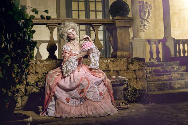 young woman in eighteenth century image posing at vintage exterior - festliche kleider kindermode stock-fotos und bilder