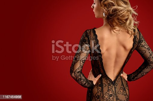 Back view of slim young female wearing black lace backless dress and holding hands on waist against bright red background