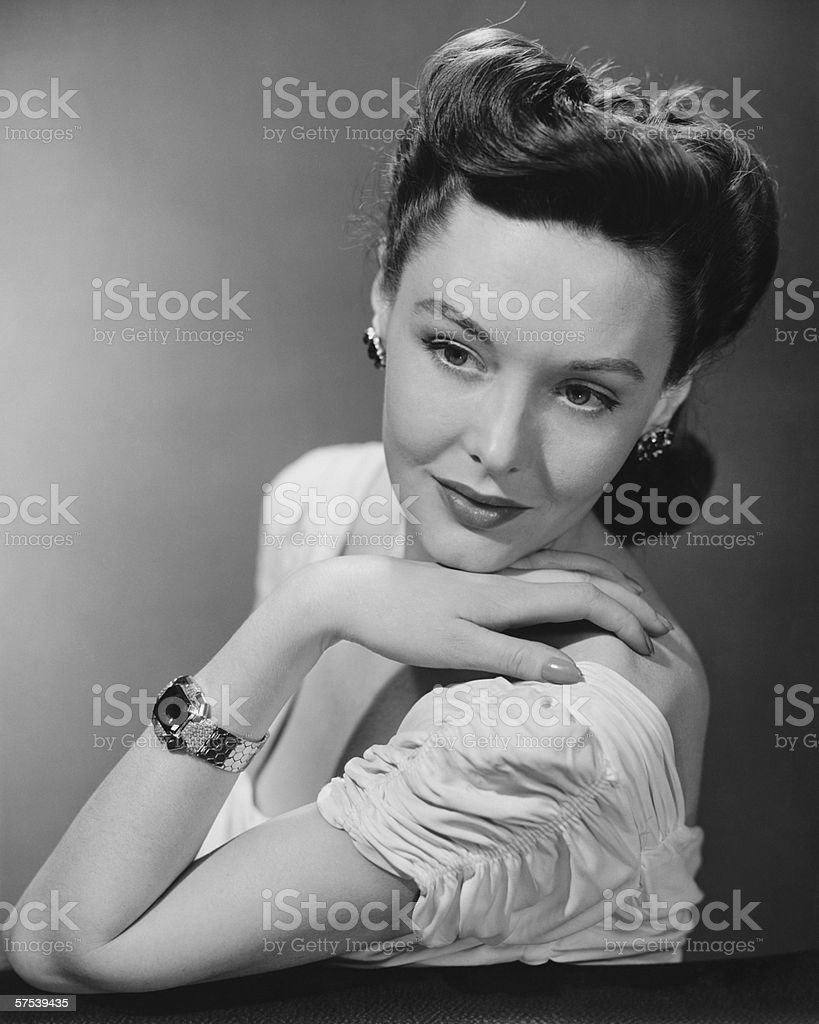 Young woman in evening wear in studio, (B&W), close-up stock photo