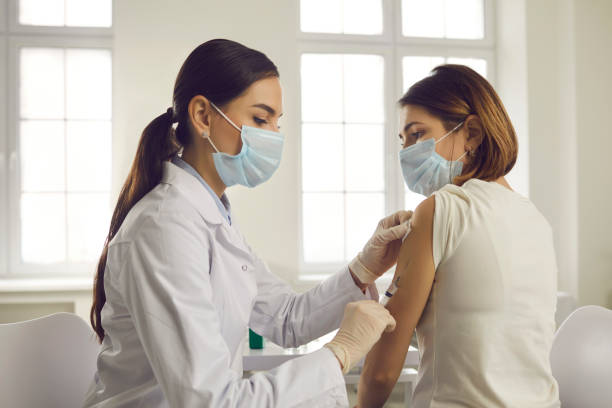 Young woman in face mask getting an antiviral vaccine at the hospital or health center stock photo